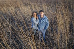Skylar and Aaron standing in a golden field, wide angle