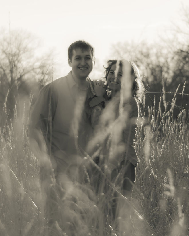 Skylar and Aaron holding each other in golden field.