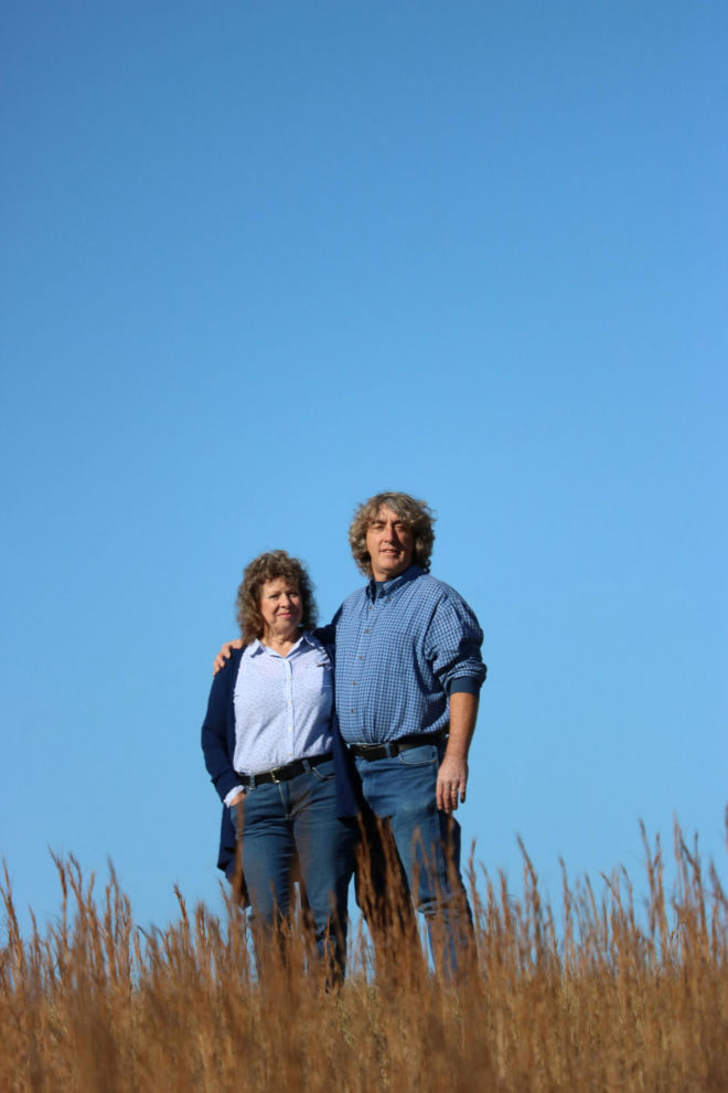 Portrait of Andy and Rose Derrickson standing in a field.