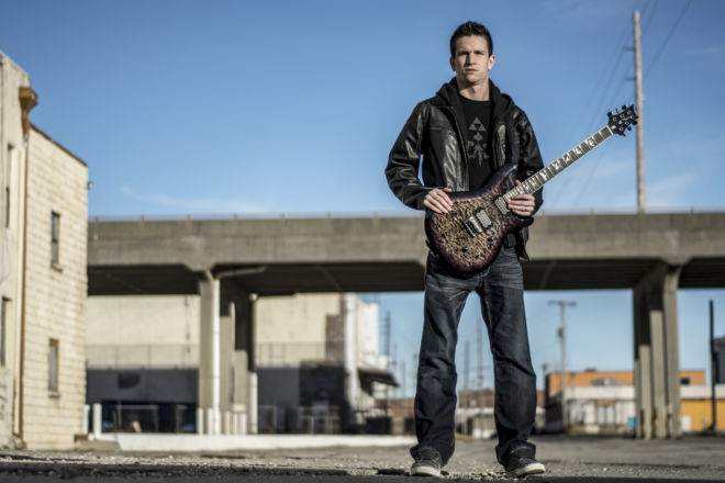 Photo of guitarist Chase Whiteside standing in an empty ally.