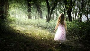 Young girl in dress walking in an enchanted forest