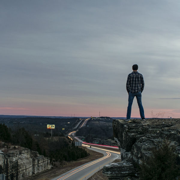 Leif derrickson stands on a small cliff edge over looking traffic on highway 65, north of Branson Missouri.