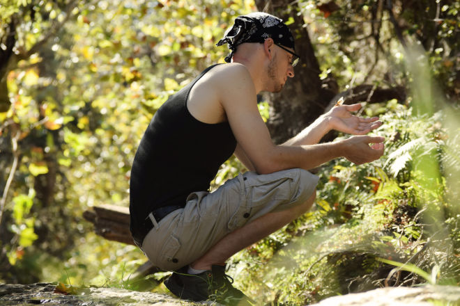 Matt Chaney kneeled down observing a dragonfly which landed on his hand.
