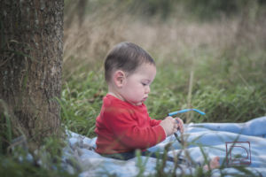 Portrait of baby Micah Hale sitting on a blanket under a tree.