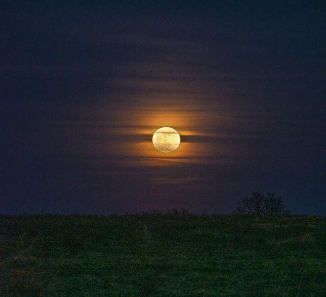 Massive full moon rising over Ozark Missouri countryside