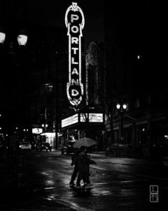 Portland theater sign illuminates a rainy city street in downtown Portland Oregan