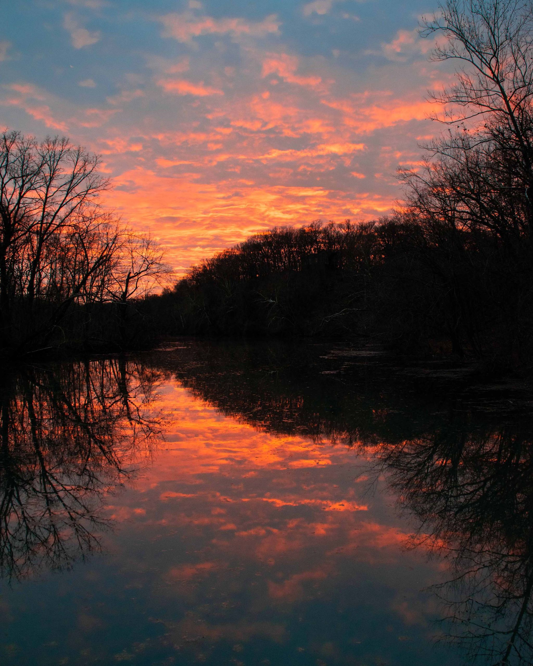 Firey orange sunset is mirrored upon the lake at Springfield Nature Center in Springfield, Missouri