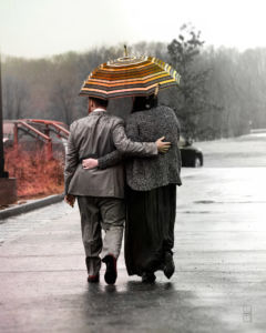 Two newly weds walking in the rain holding an umbrella