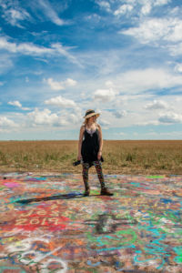 Krista Meadows stands on a colorfully spraypainted ground at Cadellac ranch just outside of Amarillo, Texas