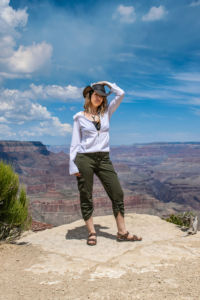 Krista Meados poses on a cliff edge overlooking the Grand Canyon