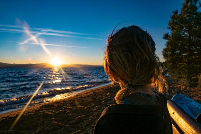 Krista Meadows looks onward at the setting sun over lake Tahoe