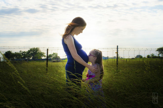 Expecting mother and daughter standing in a field.