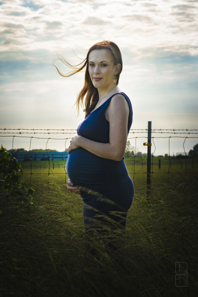 Portrait of expecting mother standing in a field.