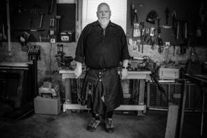Auther, Blacksmith, and Pharmacist Tony Marvin standing in his blacksmithing shop.