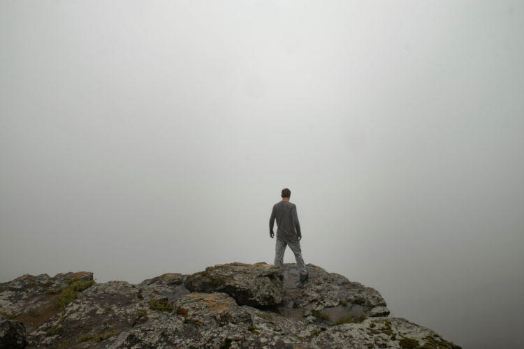 Leif derrickson stands on the very edge of a cliff at White Rock Mountain as he is engulfed in a thick white cloud.