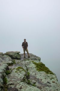 Travis Elston Standing on white rock mountain cliff edge as a thick, white cloud passes by