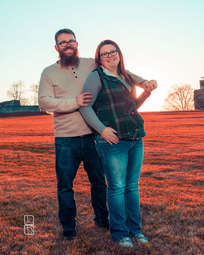 Dave and Bethany Strieff hold each other close with the sunset behind them in red hues