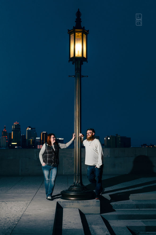 Dave and Bethany Strieff both pose near a lamp on top the world war one memorial in kansas city