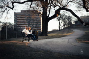 Dave and Bethany Strieff sitting on a bench near the world war 1 memorial in Kansas City