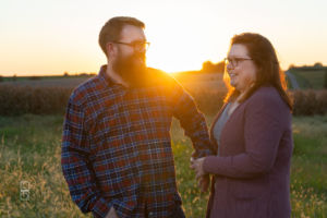 Dave and Bethany Strieff hold eahc others hand in the north missouri fields at sunset