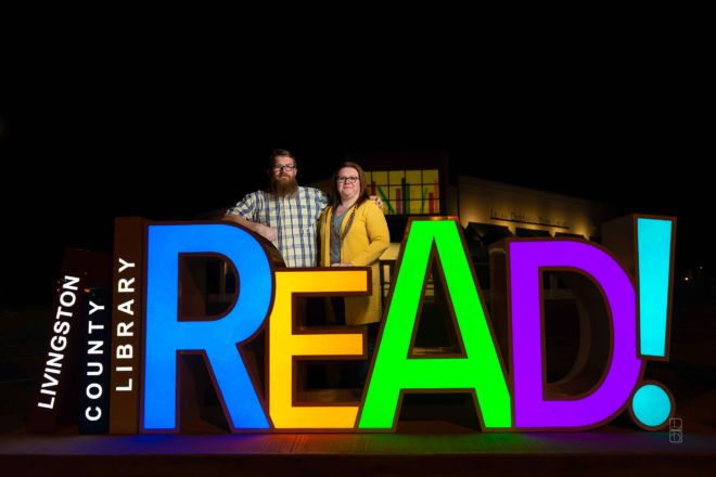 Dave and Bethany Strieff pose near the LIvingston county Missouri childrens library READ sign