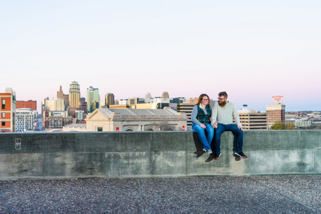 Dave and Bethany Strieff sit atop a stone wall with Kansas City skyline in the backdrop version 1