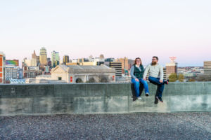 Dave and Bethany Strieff sit atop a stone wall with Kansas City skyline in the backdrop version 2