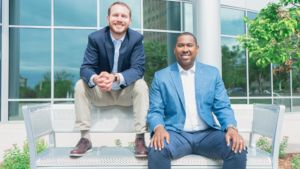 Maurice Dukes and Ryan Werking of Petrofunders sitting on a metal bench at the denver tech Center